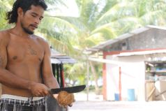 Young man cutting a coconut to prepare cobra for sale